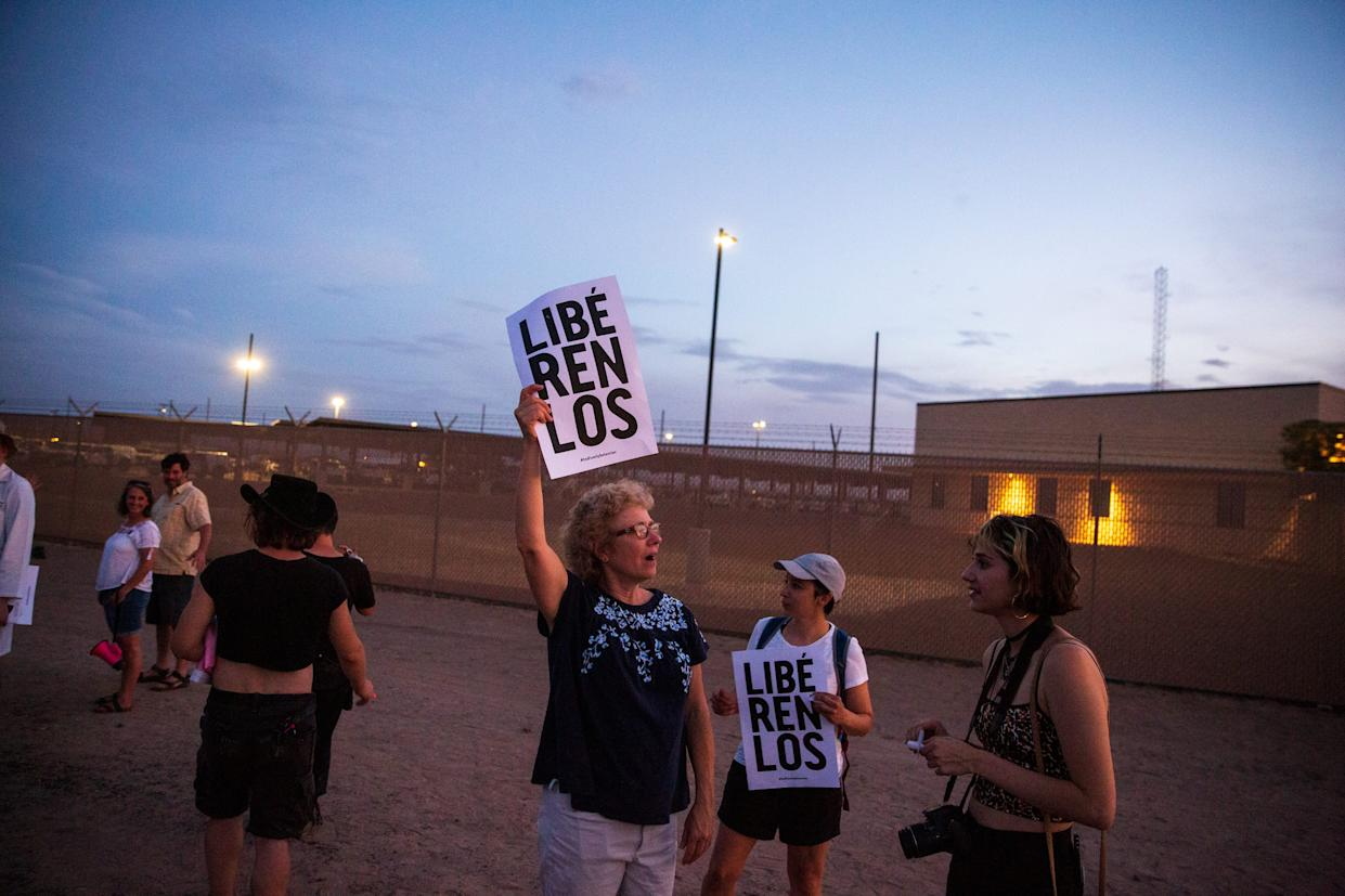 """Sue Saunders from Marin County, California, holds a sign meaning """"Free them"""" in front of the Clint, Texas, facility on July 4, 2019."""
