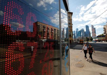Pedestrians walk past an electronic board showing currency exchange rates of the U.S. dollar and euro against Russian rouble in Moscow, Russia August 10, 2018. REUTERS/Maxim Shemetov