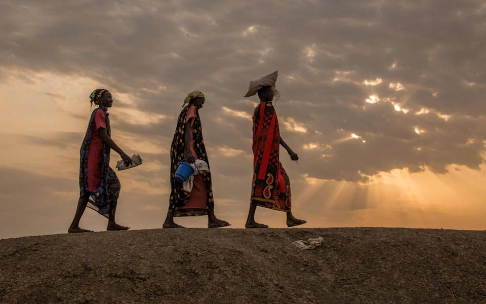 Internally displaced women walk to a food distribution in the early morning at the Protection of Civilian site (PoC) in Bentiu, South Sudan - Stefanie Glinski/AFP