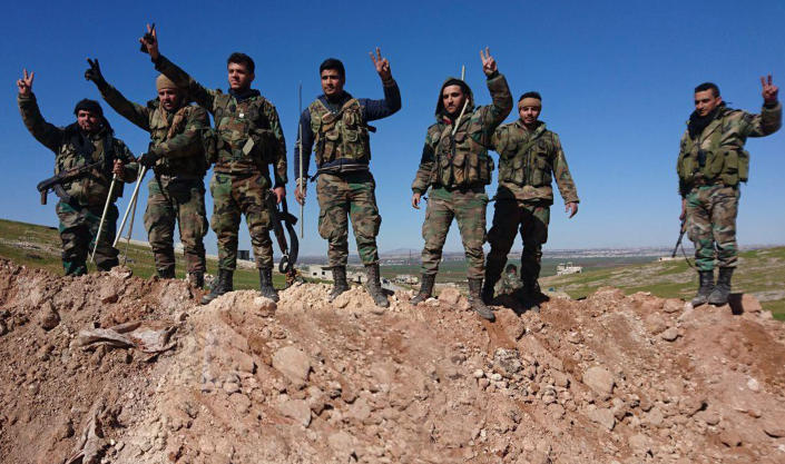 FILE - This Feb. 9, 2020, file photo released by the Syrian official news agency SANA, Syrian army soldiers flash the victory sign in the village of al-Eis, in Aleppo province, Syria. Syria's civil war has long provided a free-for-all battlefield for proxy fighters. But in its ninth year, the war is drawing major foreign actors into direct conflict, with the threat of all-out confrontations becoming a real possibility. (SANA via AP, File)