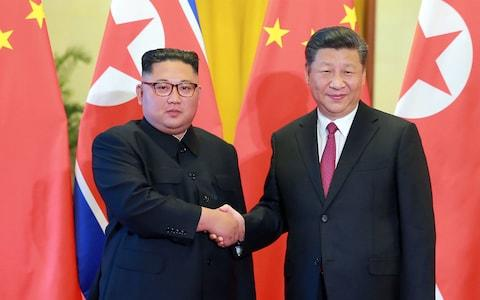 North Korean leader Kim Jong Un (L) shaking hands with Chinese President Xi Jinping at the Great Hall of the People in Beijing. - Credit: KCNA/AFP