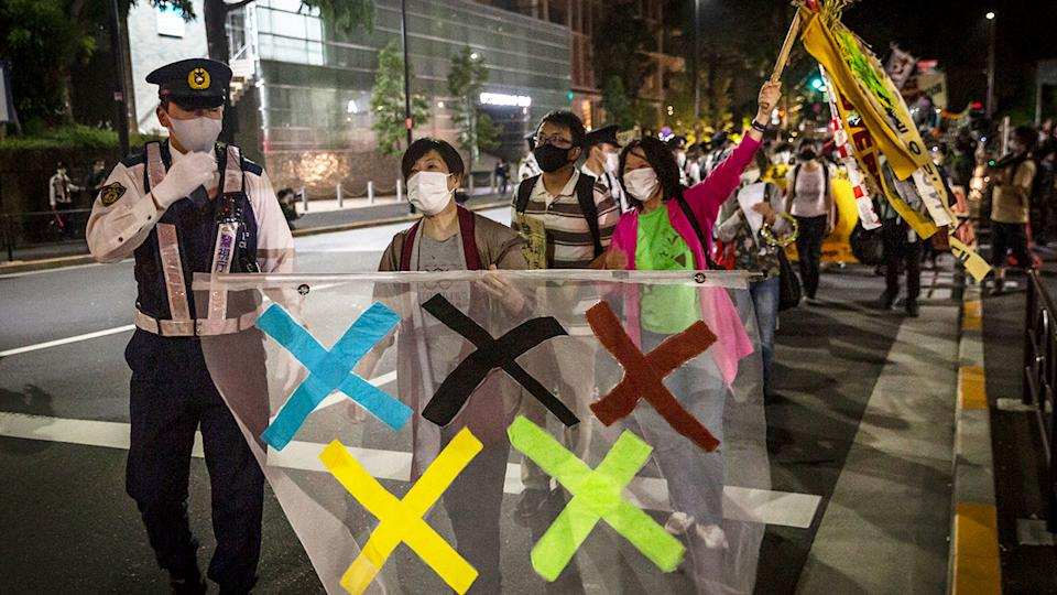 People are seen here marching on the streets in Japan to oppose the staging of the Tokyo Games.