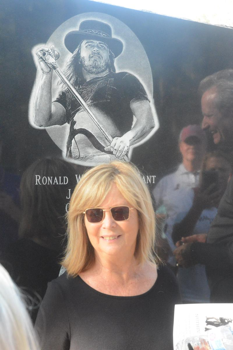 Judy Van Zant-Jenness stands below a sketch of the late Ronnie Van Zant, the original lead singer of the Southern rock band, Lynyrd Skynyrd. The sketch is part of a monument to the band members who lost their lives following a plane crash near Gillsburg, Miss., on Oct. 20, 1977. Van Zant-Jenness, his widow, helped unveil the monument at a ceremony on Oct. 20, 2019.