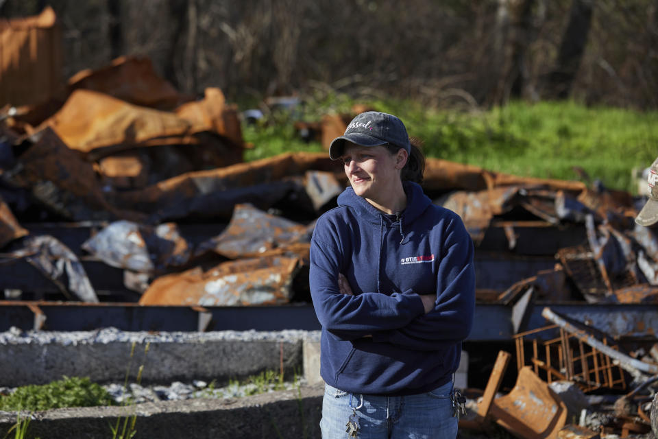 Melynda Small stands in front of a home that burned down during the Echo Mountain fire in Otis, Ore., on Thursday, May. 13, 2020. Small has dedicated her time to helping the small town on the Oregon coast recover from the devastating fire that destroyed 293 homes. Experts say the 2020 wildfire season in Oregon was a taste of what lies ahead as climate change makes blazes more likely and more destructive even in wetter, cooler climates like the Pacific Northwest. (AP Photo/Craig Mitchelldyer)