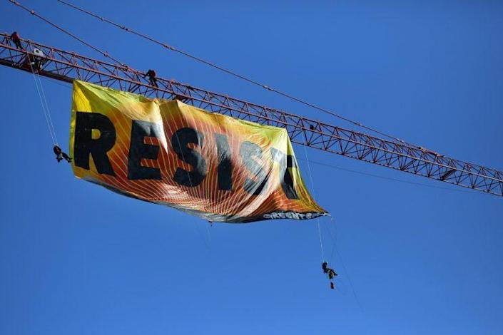 Greenpeace activists unfurl a banner from a construction crane near the White House