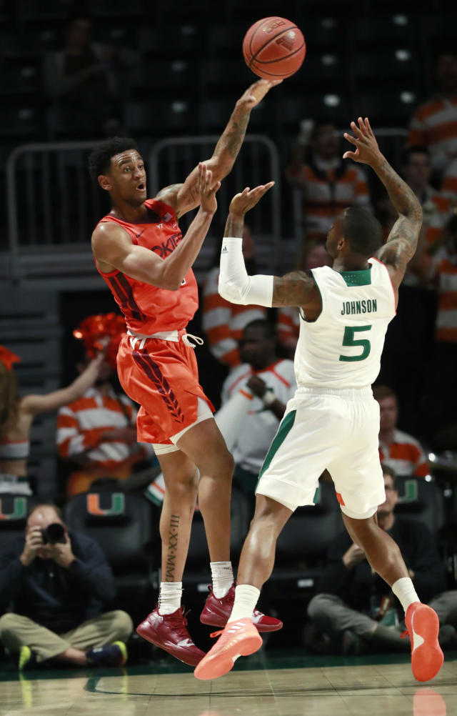 Virginia Tech guard Nickeil Alexander-Walker, left, passes the ball past Miami guard Zach Johnson (5) during the first half of an NCAA college basketball game Wednesday, Jan. 30, 2019, in Coral Gables, Fla. (AP Photo/Wilfredo Lee)