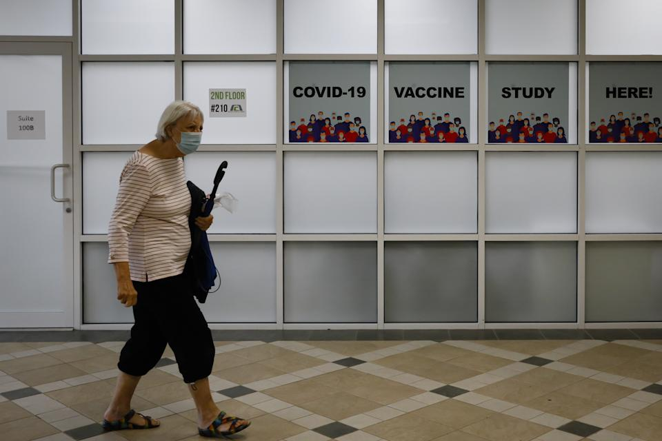 "A person wearing a face mask walks in a hallway where signs read ""COVID-19 vaccine study here!"""
