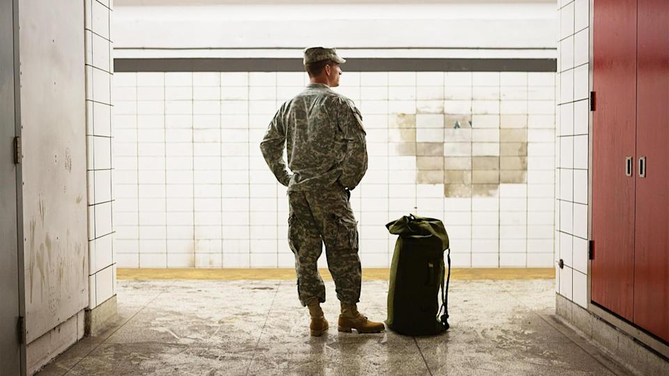 A soldier is waiting for the train.