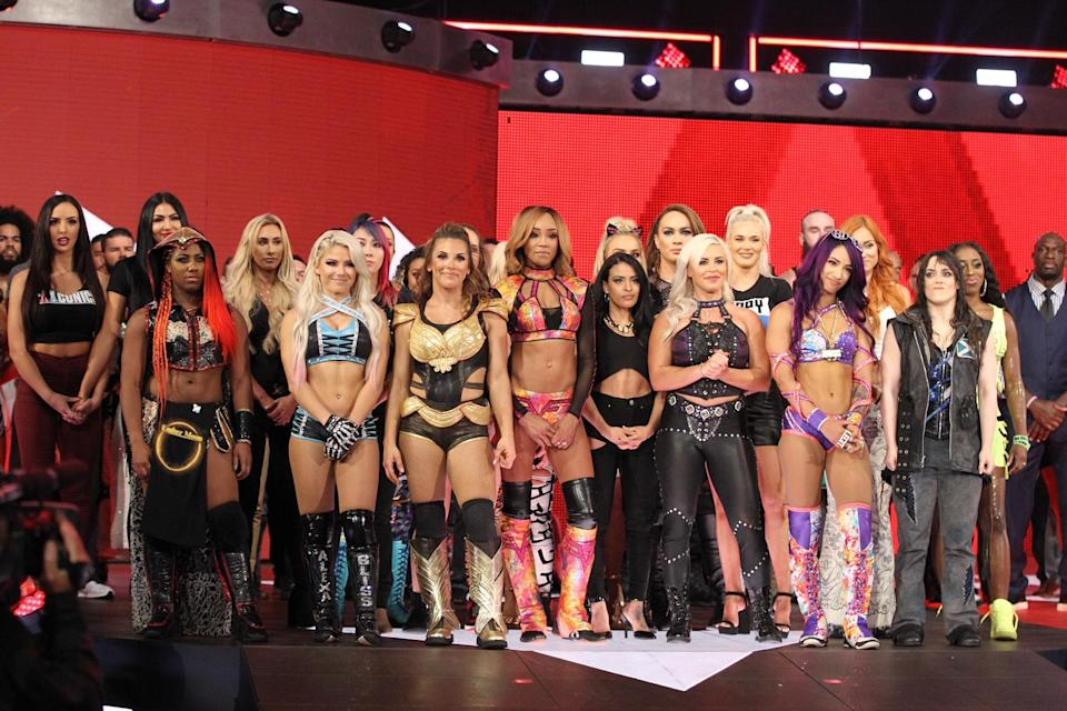 """Members of the WWE's women's division stand on stage during """"Monday Night Raw"""" as Stephanie McMahon announces the """"Evolution"""" pay-per-view event. (Photo courtesy of WWE)"""