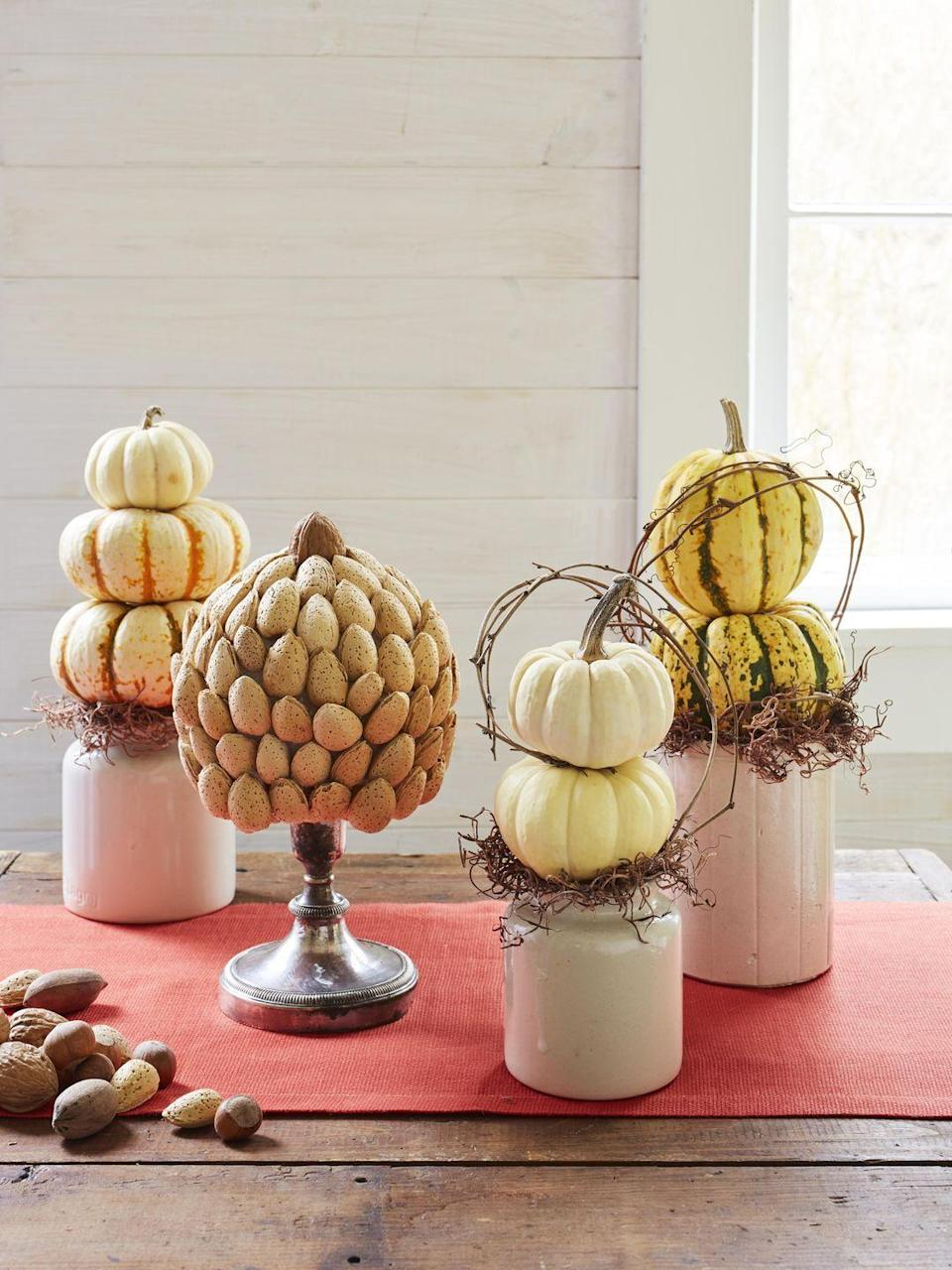 <p>Gather a grouping of these tabletop topiaries down the middle of the table or on a buffet. <br></p><p><strong>To make the nut topiaries:</strong> Lightly spray styrofoam craft balls with brown paint. Once dry, hot glue nuts to styrofoam balls in an orderly pattern, as shown. For the walnut topiary, start with a middle equator row and add rows up and down from there. Add hazelnuts to fill any gaps. For the raw almond topiary, start at the top and work your way down, gluing horizontal rows around the perimeter and overlapping slightly for full coverage. Leave space at bottom to rest on top of candlestick bases. Attach with hot glue, as needed.<strong><br></strong></p><p><strong>To make the pumpkin and squash topiaries: </strong>Remove stems, except for the top pieces. Stack two pumpkins and secure using small wooden skewers or toothpicks. Skewer the bottom piece and place into crocks filled with floral foam. Cover foam with Spanish moss, and finish with grapevine accents.</p>