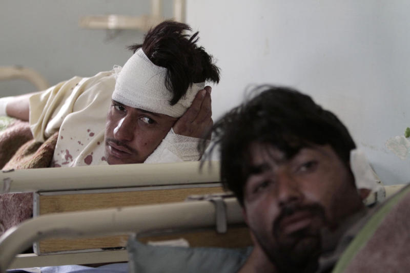FILE - In this file photo taken Thursday, Nov. 28, 2013, Afghans are treated at Ghanikhel district hospital after two roadside bombs in the Achin district of Jalalabad, east of Kabul, Afghanistan. The number of children killed and wounded in Afghanistan's war jumped by 34 percent in 2013 as the Taliban intensified armed attacks across the country and continued to lay thousands of roadside bombs, according to a U.N. report Saturday, Feb. 8, 2014. (AP Photo/Rahmat Gul, File)