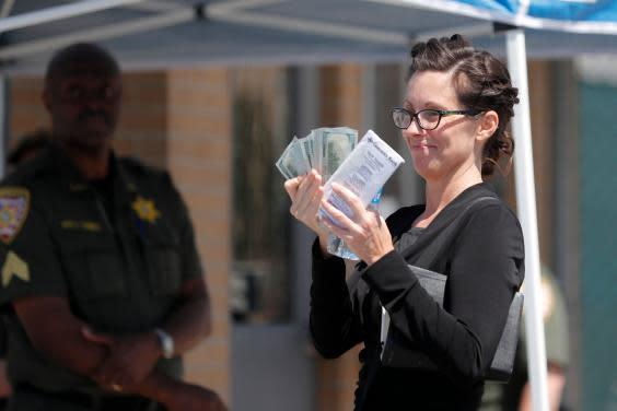 Shaye Spell, wife of Lousiana pastor Tony Spell, flashes wads of cash as she arrives at the East Baton Rouge parish jail to post bond for him following his arrest for flouting coronavirus lockdown orders (AP)