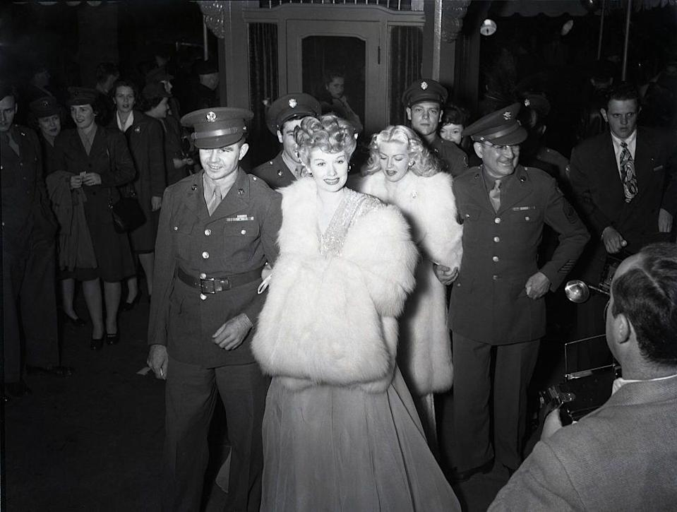 <p>A soldier escorts Lucille Ball down the red carpet at the premiere of <em>Show Business</em> in 1944. </p>