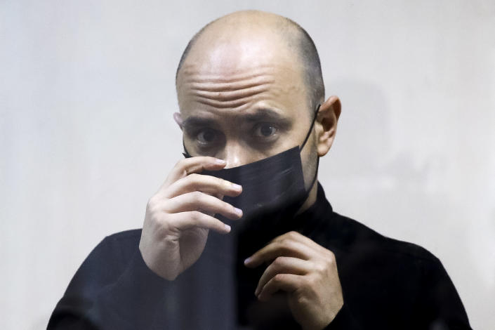 """Andrei Pivovarov, the head of Open Russia movement attaches a face mask to protect against coronavirus standing behind the glass during a court session in Krasnodar, Russia, Wednesday, June 2, 2021. In the southern city of Krasnodar, a court was scheduled to consider whether to keep Andrei Pivovarov, the head of the Open Russia movement, in custody pending an investigation. Pivovarov was pulled off a Warsaw-bound plane at St. Petersburg's airport just before takeoff late Monday and taken to Krasnodar, where authorities accused him of supporting a local election candidate last year on behalf of an """"undesirable"""" organization. (AP Photo)"""