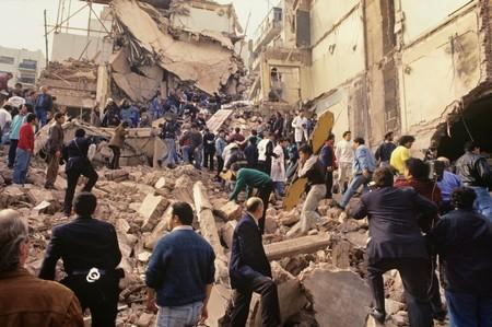 Rescue workers work after an explosives-laden truck blew up outside the Argentine Israeli Mutual Association (AMIA) building on July 18 1994, in Buenos Aires