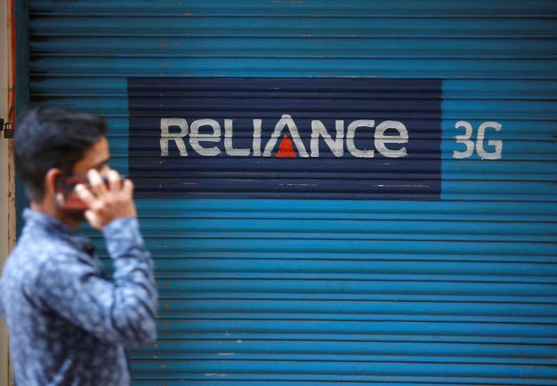 FILE PHOTO: A man speaks on his mobile phone as he walks past a closed shop painted with an advertisement of Reliance Communications in Mumbai