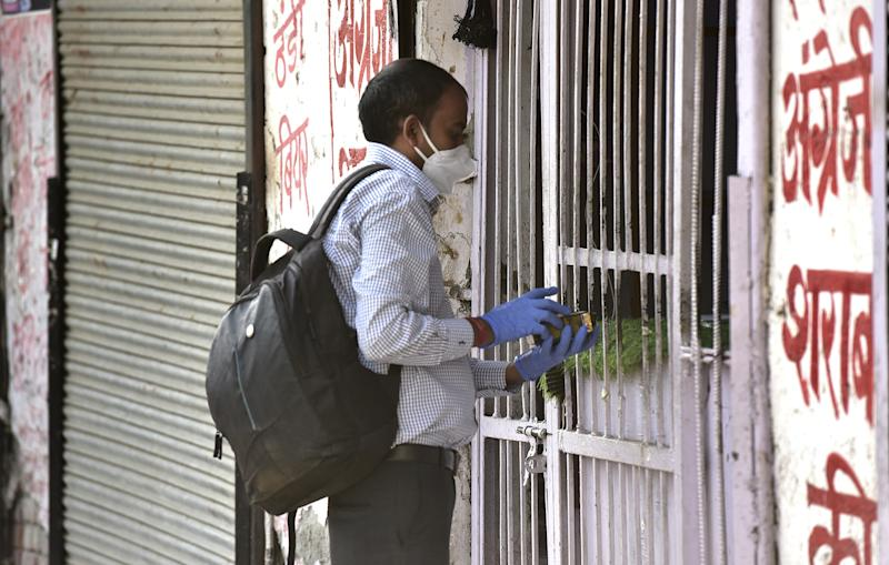 NOIDA, INDIA MAY 6: A man buys alcohol from a liquor store during lockdown, on May 6, 2020 in Noida, India. (Photo by Virendra Singh Gosain/Hindustan Times via Getty Images)