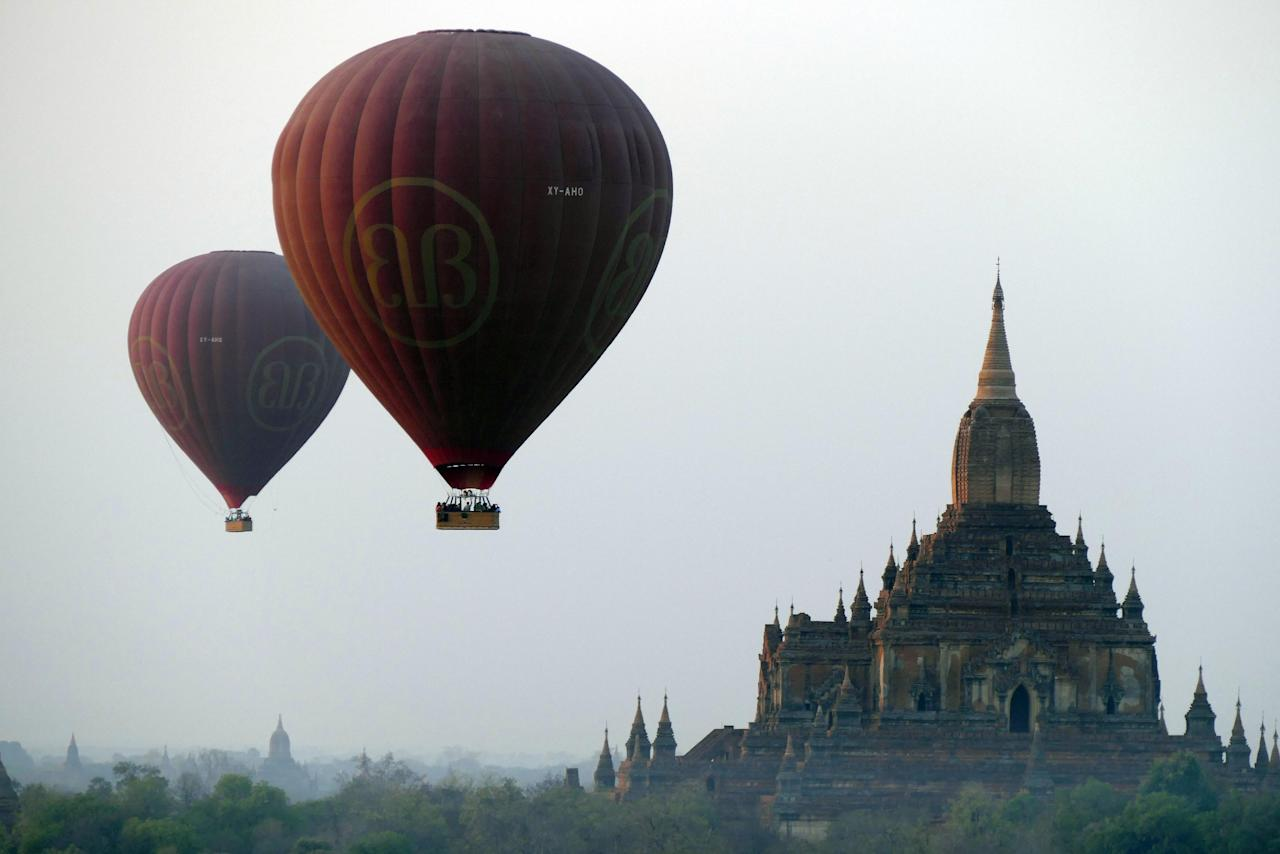 FILE - In this Tuesday Feb. 24, 2015, file photo, Balloons carrying tourists fly near old temples in Bagan, Myanmar. A powerful earthquake measuring magnitude 6.8 shook central Myanmar on Wednesday, Aug. 24, 2016, damaging scores of ancient Buddhist pagodas in the former capital of Bagan, a major tourist attraction, officials said.(AP Photo/Khin Maung Win, File)