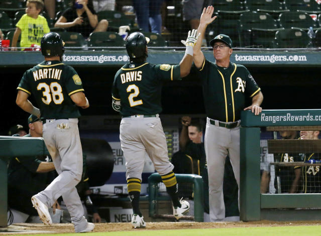 FILE - In this Tuesday, July 24, 2018, file photo, Oakland Athletics manager Bob Melvin, right, gives Khris Davis (2) a high-five after Davis' three-run home run in the 10th inning of a baseball game against the Texas Rangers in Arlington, Texas. The A's won 13-10. Never before in his managerial career has Melvin been around a team with such a knack for comebacks, for winning the close ones in the late innings despite what might seem insurmountable odds. (AP Photo/Roger Steinman, File)