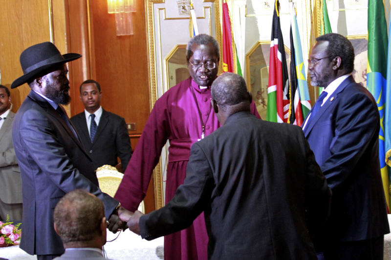 South Sudan's President Salva Kiir, left, and rebel leader Riek Machar, right, shake hands and pray before signing an agreement of the cease-fire of the conflict in South Sudan in Addis Ababa, Ethiopia, Friday, May 9, 2014. The South Sudan's president has reached a cease-fire agreement with the rebel leader, an African regional bloc said Friday, after a vicious cycle of revenge killings drew international alarm. (AP Photo/Elias Asmare)