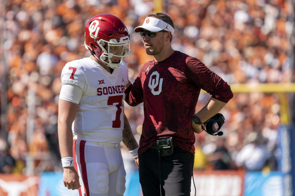 Oklahoma head coach Lincoln Riley talks to quarterback Spencer Rattler before sending Rattler in for a two-point conversion during the second half of an NCAA college football game against Texas at the Cotton Bowl, Saturday, Oct. 9, 2021, in Dallas. (AP Photo/Jeffrey McWhorter)