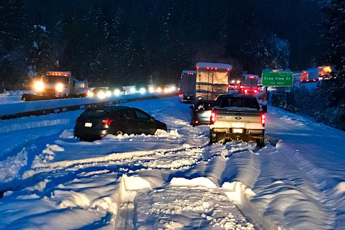 """Cars and trucks in stopped traffic on Interstate 5 near Dunsmuir, California, on Nov. 26, 2019. A """"bomb cyclone,"""" which triggers a rapid drop in air pressure, brought snow to the mountains and wind and rain along the California and Oregon coasts."""