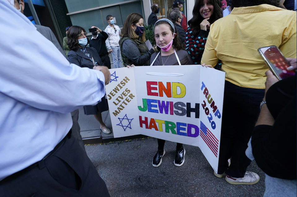 """FILE - In this Thursday, Oct. 15, 2020 file photo, a young girl holds a poster she made as she prepares to pose for a cell phone photograph for a relative as she and others joined protesters outside the offices of New York Gov. Andrew Cuomo in New York. Three Rockland County Jewish congregations are suing New York state and Cuomo, saying he engaged in a """"streak of anti-Semitic discrimination"""" with a recent crackdown on religious gatherings to reduce the state's coronavirus infection rate. (AP Photo/Kathy Willens)"""