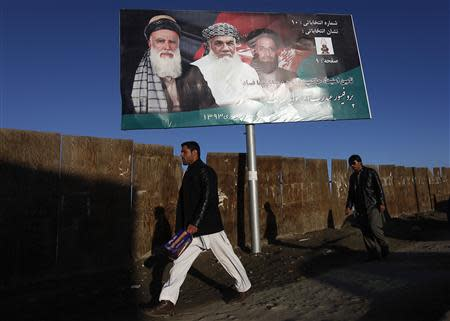 Men walk past a campaign banner of Afghan presidential candidate Abdul Rassoul Sayyaf, in Kabul