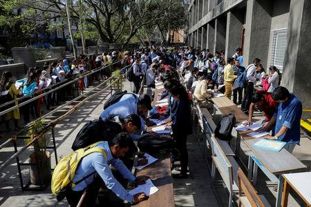 FILE PHOTO: Job seekers fill up forms as others line up for registration during a job fair in Chinchwad