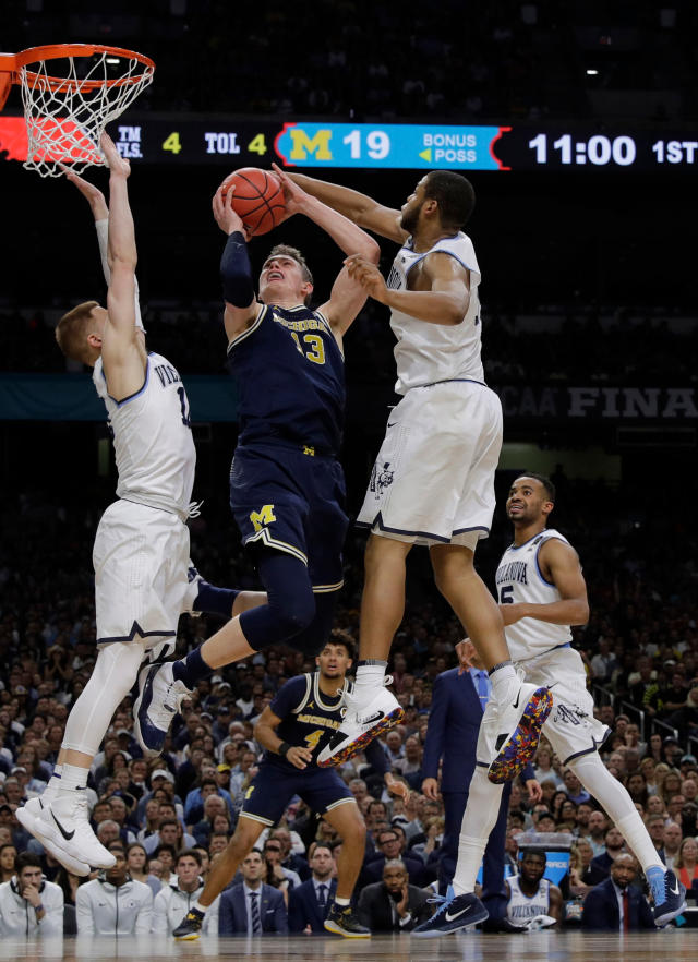 Michigan forward Moritz Wagner, center, drives to the basket between Villanova defenders Donte DiVincenzo, left, and Omari Spellman, right, during the first half in the championship game of the Final Four NCAA college basketball tournament, Monday, April 2, 2018, in San Antonio. (AP Photo/David J. Phillip)