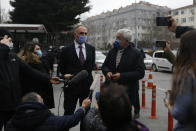 Turkish pilot Noyan Pasin, left, who was sentenced to four years and two months in prison for flying former Nissan Motor Co. chairman Carlos Ghosn out of Japan in 2019 during his dramatic escape to Beirut, Lebanon via Istanbul talks to media as his lawyer looks on, following the trial outside the court in Istanbul, Wednesday, Feb. 24, 2021. The court convicted a Turkish private airline official and two pilots. Ghosn, who was arrested over financial misconduct allegations in Tokyo in 2018, skipped bail while awaiting trial there. (AP Photo/Mehmet Guzel)