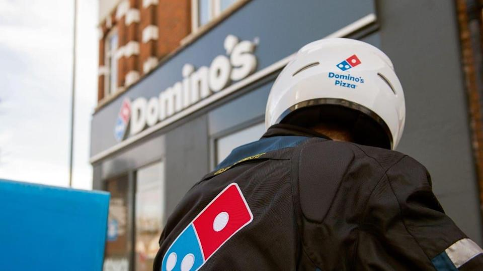 A rider sits outside a Domino's store