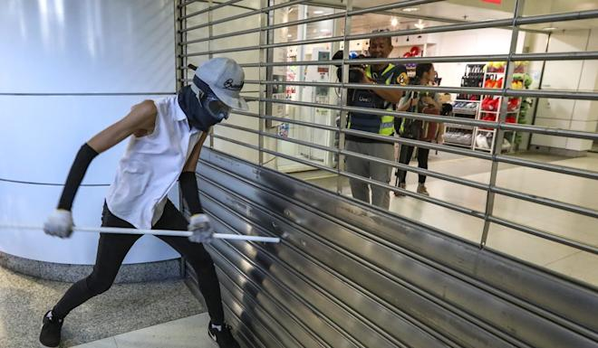 A protester attempts to open a gate at Tsing Yi MTR station. Photo: Felix Wong