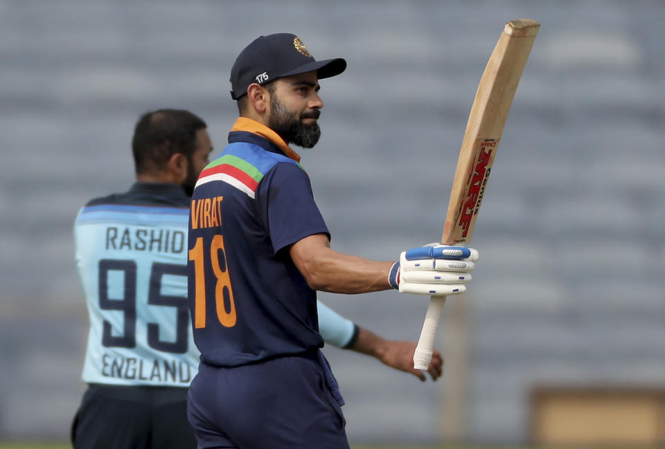 India's captain Virat Kohli, right, raises his bat to celebrate scoring fifty runs during the first One Day International cricket match between India and England at Maharashtra Cricket Association Stadium in Pune, India, Tuesday, March 23, 2021. (AP Photo/Rafiq Maqbool)