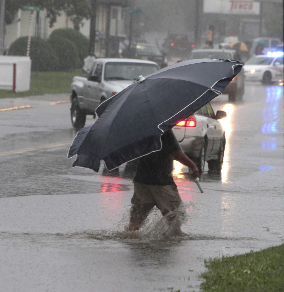 A pedestrian uses a beach umbrella to keep off the rain from tropical storm Irene on Sunday, Aug. 28, 2011 in Barre, Vt. Irene weakened to winds of 60 mph, well below the 74 mph dividing line between a hurricane and tropical storm. The system was still massive and powerful, forming a figure six that covered the Northeast. It was moving twice as fast as the day before. (AP Photo/Toby Talbot)