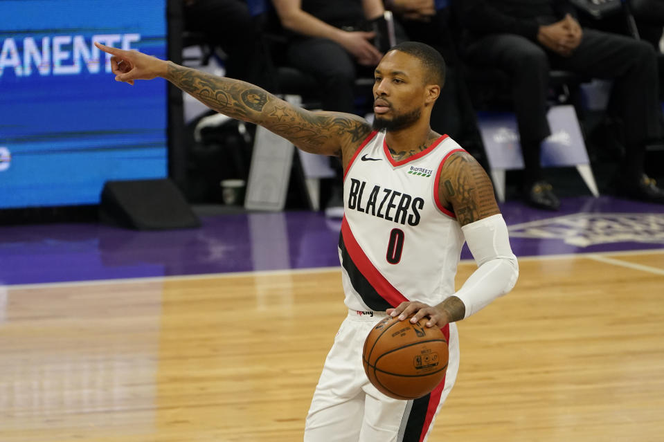 Portland Trail Blazers guard Damian Lillard gestures to teammates during the first quarter of the team's NBA basketball game against the Sacramento Kings in Sacramento, Calif., Wednesday, Jan. 13, 2021. The Trail Blazers won 132-126. (AP Photo/Rich Pedroncelli)