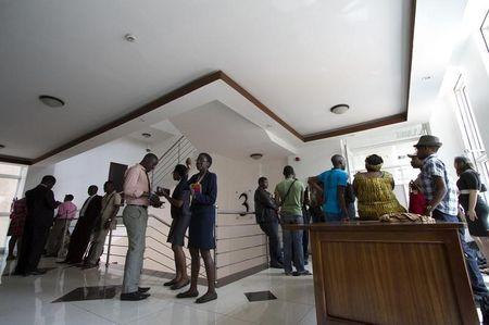 Gay and human rights activists wait outside the courts before filing a constitutional petition against a new anti-homosexuality law, in Kampala