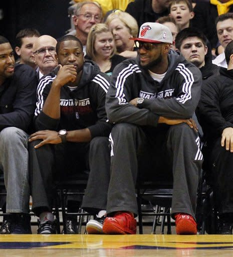 Miami Heat's Lebron James, right, and Dwyane Wade attend an NCAA college basketball game between Marquette and Seton Hall, Tuesday, Jan. 31, 2012, in Milwaukee. (AP Photo/Jeffrey Phelps)
