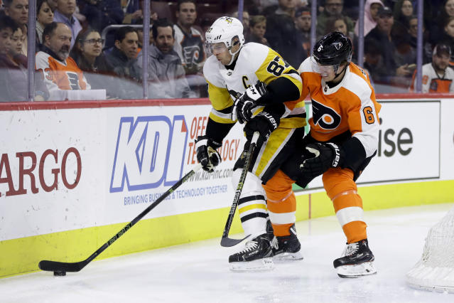 Pittsburgh Penguins' Sidney Crosby (87) and Philadelphia Flyers' Travis Sanheim (6) battle for the puck during the first period of an NHL hockey game, Monday, Feb. 11, 2019, in Philadelphia. (AP Photo/Matt Slocum)