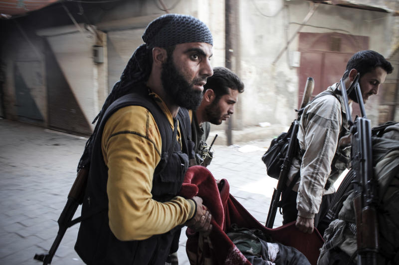 In this Tuesday, Oct. 30, 2012 photo, Syrian rebels carry a wounded comrade in a blanket away from the frontline in the town of Harem, Syria. (AP Photo/Mustafa Karali)