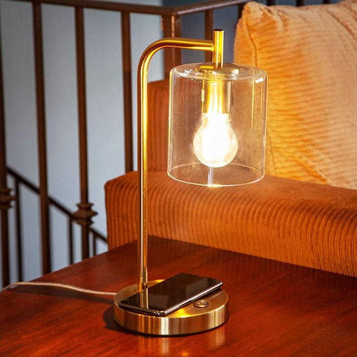 """With a touch of mid-century modern design, this office lamp has a brass finish and glass shade so it'll actually shine at your desk. This lamp has a wireless charging pad for your phone. It can work with Alexa and Google Home Assistant, too. And don't worry, it comes with its own LED bulb already. <a href=""""https://amzn.to/2RrBklh"""" rel=""""nofollow noopener"""" target=""""_blank"""" data-ylk=""""slk:Find it for $65 at Amazon"""" class=""""link rapid-noclick-resp"""">Find it for $65 at Amazon</a>."""