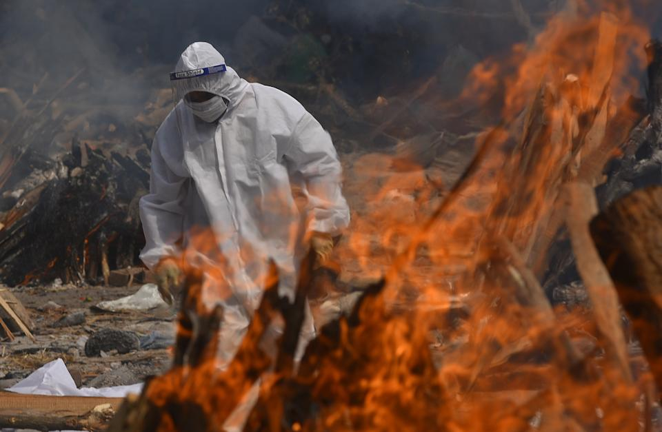A family member, wearing a Personal Protective Equipment (PPE), performs the last rites for Covid-19 victims at a cremation ground in New Delhi.