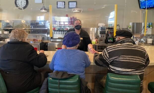 Customers at Maid Marian's Diner in Charlottetown sit at the counter seperated from staff by a clear plastic barrier.