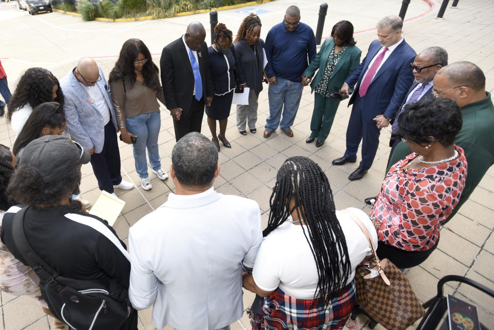 Descendants of Henrietta Lacks, whose cells, known as HeLa cells, have been used in medical research without her permission, say a prayer with attorneys outside the federal courthouse in Baltimore, Monday, Oct. 4, 2021. They announced during a news conference that Lacks' estate is filing a lawsuit against Thermo Fisher Scientific for using HeLa cells. (AP Photo/Steve Ruark)
