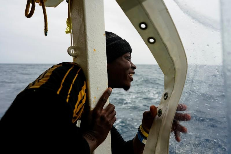 A migrant looks at the island of Sicily on board a NGO Proactiva Open Arms rescue boat in the central Mediterranean Sea
