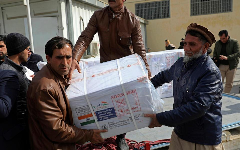 Afghan health ministry workers unload boxes of vaccines - Rahmat Gul/AP