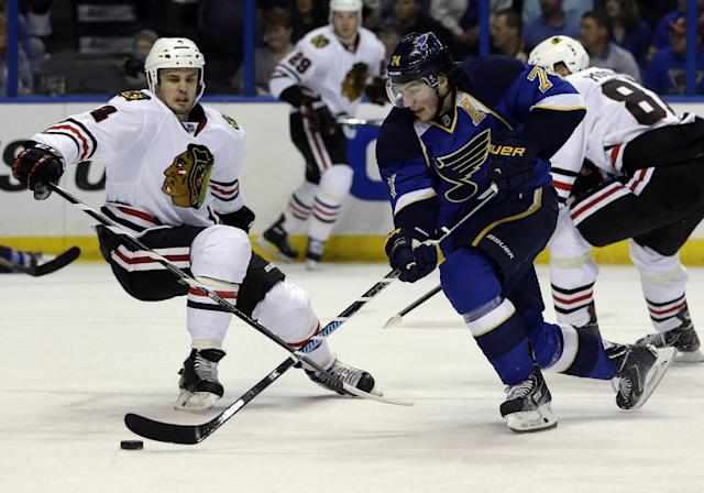 St. Louis Blues' T.J. Oshie, right, slips past Chicago Blackhawks' Niklas Hjalmarsson, of Sweden, on his way to score during the second period in Game 5 of a first-round NHL hockey playoff series Friday, April 25, 2014, in St. Louis. (AP Photo/Jeff Roberson)