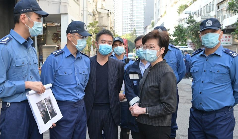 Chief Executive Carrie Lam with the Director of Fire Services Joseph Leung (second left); Yau Tsim Mong district officer Edward Yu (centre); and Buildings Director Yu Tak-cheung (behind Lam). Photo: Handout