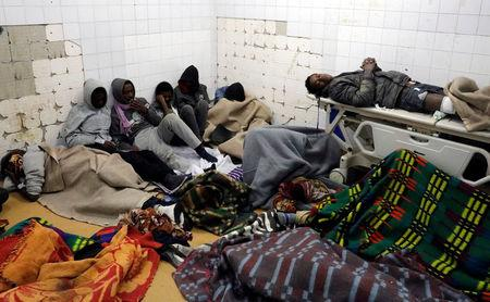 Migrants who were injured in a truck crash, are seen at a hospital in Bani Walid town