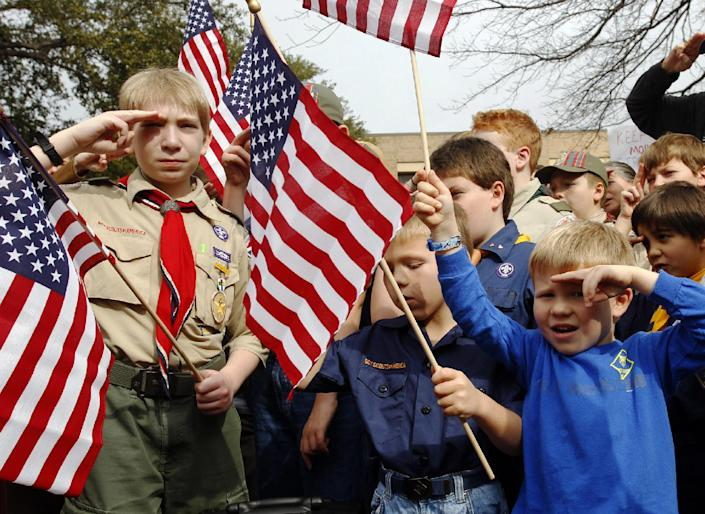 """FILE - In this Feb. 6, 2013 file photo, from left, Joshua Kusterer, 12, Nach Mitschke, 6, and Wyatt Mitschke, 4, salute as they recite the pledge of allegiance during the """"Save Our Scouts"""" prayer vigil and rally against allowing gays in the organization in front of the Boy Scouts of America National Headquarters in Dallas, Texas. The BSA said Wednesday, Feb. 12, 2014 that it lost 6 percent of its membership after an often-bruising year in which it announced it would accept openly gay boys for the first time, over the objections of some participants who eventually left the organization. (AP Photo/Richard Rodriguez, File)"""